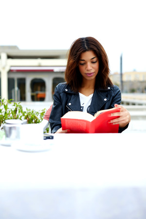 Attractie female hipster enjoying a good book in cafe during her recreation time at weekend, lovely young woman read novel sitting at the table of coffee shop, student engage leisure time for reading
