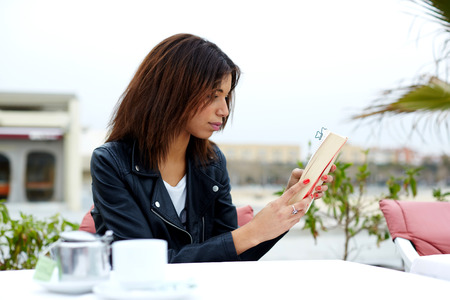 autodidact: Portrait of young lovely female enjoying a good book while sitting at the table in coffee shop terrace, charming afro american woman reading novel or book during her recreation time at weekend