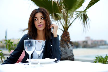 area sexy: Charming afro american woman smoking cigarette while sitting at sidewalk cafe looking pensive, female tourist enjoying her recreation time in restaurant on seashore with palm tree on background Stock Photo