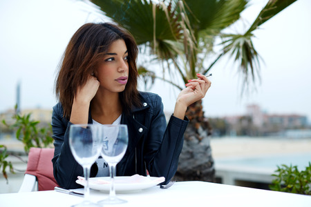 area sexy: Attractive afro american woman smoking cigarette while sitting at sidewalk cafe looking pensive, female tourist enjoying her recreation time in restaurant on seashore with palm tree on background Stock Photo