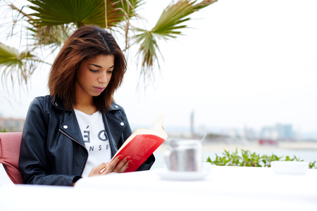 autodidact: Attractive afro american woman enjoying a interesting book or novel while sitting at cafe terrace, young female hipster fascinating read book in open air coffee shop during her recreation time