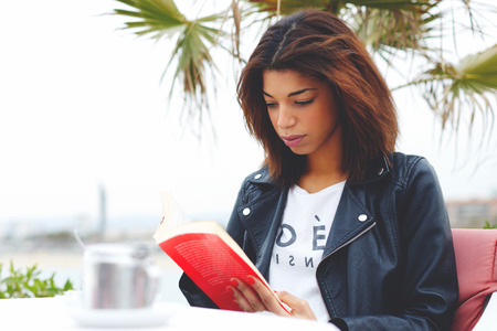 autodidact: Young lovely woman sitting at coffee shop terrace pensive reading interesting book, afro american female enjoying a good book or novel during her recreation time outdoors at weekend Stock Photo