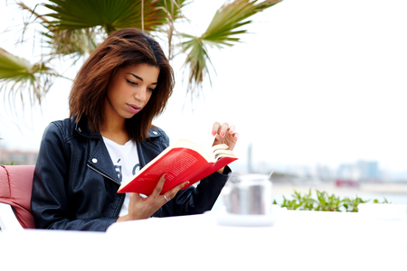 Attractive afro-american female reading fascinating book while sitting on the terrace of coffee shop, young brunette woman relaxing at weekend while read interesting book outdoors in cafe restaurant Stock Photo