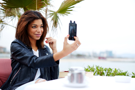 feeling good: Female tourist using mobile phone camera for take a picture of herself during vacation holidays in Barcelona, stylish afro american woman taking self portrait with smartphone, feeling good and happy