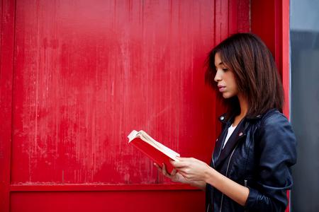 mujer leyendo libro: Joven estudiante de lectura interesante libro mientras está de pie en la ciudad en la pared de fondo rojo con copia espacio para su mensaje de texto, La mujer afroamericana leer la literatura mientras está de pie al aire libre