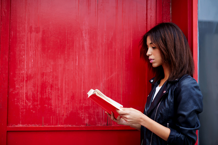interesting: Young female student reading interesting book while standing in the city on red wall background with copy space for your text message, afro american woman read literature while standing outdoors