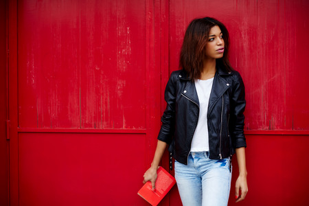 bright color: Attractive afro american female posing on red wall background in urban setting, young woman holding book in the hand while strolling in the city at her recreation time,copy space for your text message