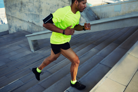 man exercise: Cropped shot male dark-skinned athlete running up a flight of stairs with speed, sporty young man in fluorescent t-shirt training or working out outdoors while jogging up the steps, filtered image