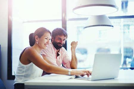 juventud: Un par de profesionales de la oficina joven que habla sobre un ordenador port�til, dos hombres de negocios la discusi�n de ideas en el espacio de co-trabajo con un ordenador port�til u ordenador port�til delante de ellos, estudiantes que trabajan con el ordenador port�til