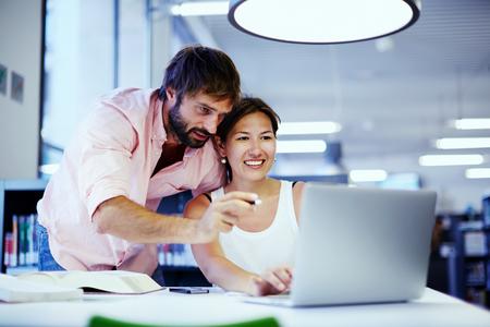 information technology: Joven empresaria asi�tica de algunos consejos de compa�ero de oficina en su escritorio, un par de empresarios profundidad de debate antes de un ordenador port�til en un sal�n social, los estudiantes hablando juntos sobre la computadora