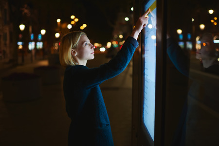 remittances: Smart city technology concept, young woman using modern urban application of bus stop in Barcelona for find out schedule of transport, female touching big digital screen which reflecting light Stock Photo