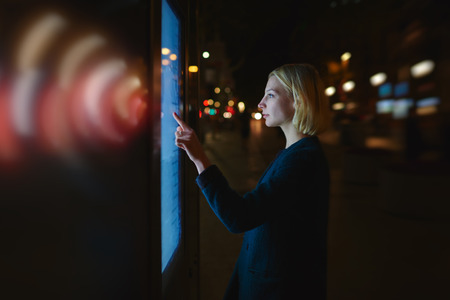 automated teller machine: Female with wireless sign symbol of lights touching big digital screen of automated teller machine while standing in night city, woman verifies her account balance on banking application modern device Stock Photo