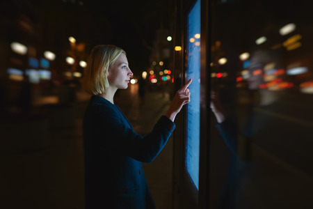 remittances: Female using automated teller machine with big digital screen while standing in night city with motion out-of-focus lights, woman verifies account balance on banking application via modern device icon Stock Photo