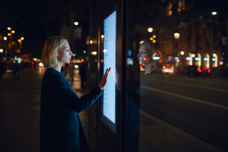 Smart city technology concept, young woman using modern urban application of bus stop in Barcelona for find out schedule of transport, female touching big digital screen which reflecting light Imagens