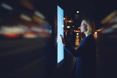 wireless data: Motion blur effect, female using automated teller machine with big digital screen while standing in night city out-of-focus lights,woman verifies account balance on banking application modern device