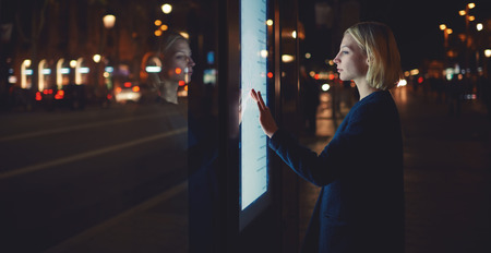 remittances: Panoramic shot, smart city technology concept,woman using modern urban application of bus stop in Barcelona for find out schedule of transport,female touching big digital screen which reflecting light