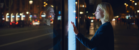 remittances: Panoramic picture,female using automated teller machine with big digital screen while standing in night city out-of-focus lights,woman verifies account balance on banking application via modern device