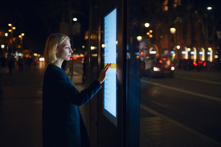 remittances: Caucasian female using automated teller machine with big digital screen while standing in night city out-of-focus lights, woman verifies account balance on banking application via modern device icon Stock Photo