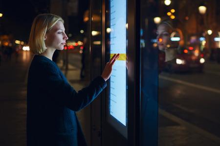 joven tocando la pantalla sensible al seleccionar la opción en la lista para averiguar horarios de transporte de la ciudad, con parada de autobús inteligente en Barcelona, ??hembra de pie en pantalla grande, que refleja la luz Foto de archivo
