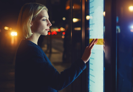 remittances: Female using automated teller machine with big digital screen while standing in night city out-of-focus lights,woman verifies account balance on banking application via modern device, filtered image Stock Photo