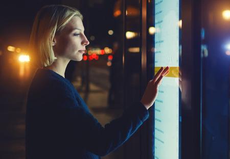Femmina che utilizza il bancomat con grande schermo digitale mentre si trova in una città notturna, le luci sfuocate, la donna verifica il saldo del conto sull'applicazione bancaria tramite dispositivo moderno, immagine filtrata Archivio Fotografico - 57553201