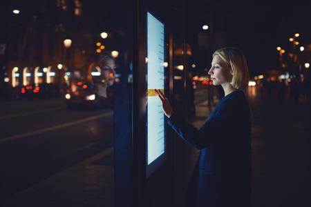 Fiatal nő, megható érzékeny képernyőt, miközben opció kiválasztásával a listán megtudja menetrend a városi közlekedésben az intelligens megálló busz Barcelonában, női állt a nagy kijelző, mely a fényt