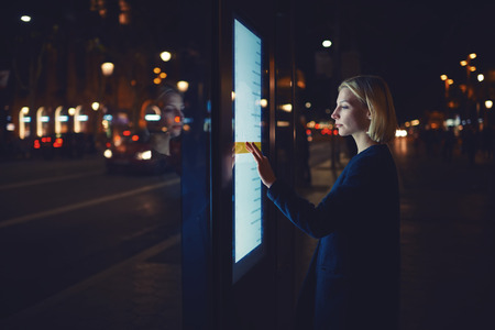 woman stop: Young woman touching sensitive screen while selecting option on the list for find out schedule of city transport with smart stop bus in Barcelona, female standing at big display which reflecting light