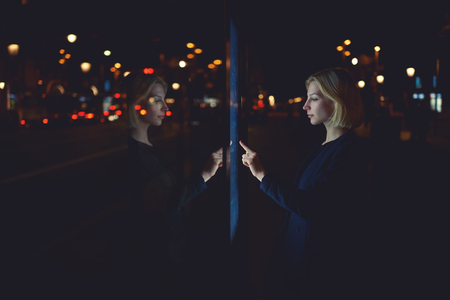 remittances: Gorgeous young woman touching digital display of smart modern bus station, female caucasian using city computer for touristic information while standing at night with urban lights on background