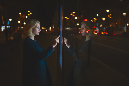remittances: Gorgeous caucasian businesswoman touching sensitive screen of smart city bus stop in night city with out-of-focus lights, female doing internet money payment with automated teller machine,filter image
