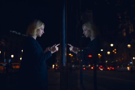 Young caucasian woman touching sensitive screen of smart city bus stop in night city with out-of-focus lights, female doing internet money payment with automated teller machine holding mobile phone Фото со стока - 57582752