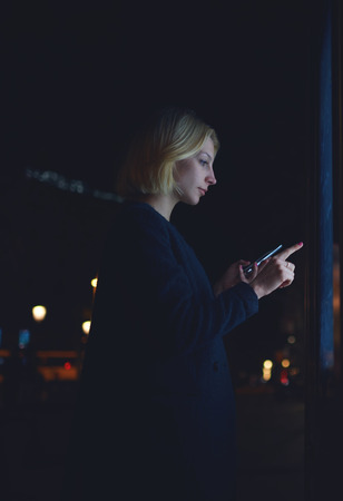 automated teller machine: Young woman touching big digital display while standing in night city with reflected on her face screen light, female doing internet money payment with automated teller machine holding smartphone