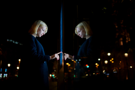 bokeh lights: Blonde caucasian businesswoman touching sensitive screen of smart city bus stop in night city with out-of-focus lights, young female doing internet money payment with automated teller machine Stock Photo