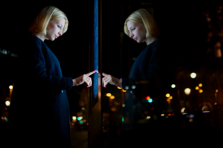 automated teller: Caucasian female using automated teller machine with big digital screen while standing in night city out-of-focus lights, woman verifies account balance on banking application via modern device icon Stock Photo