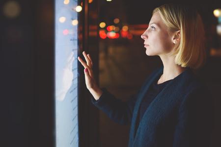 Intelligent concept technologique de la ville, jeune femme utilisant l'application urbaine moderne de l'arrêt de bus à Barcelone pour découvrir le calendrier des transports, grand écran numérique touchante femelle qui réfléchit la lumière, le filtre