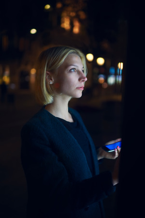 automated teller machine: Portrait of caucasian young woman realize internet money payment with automated teller machine while holding mobile phone in the hand, female strolling in night city with out-of-focus lights