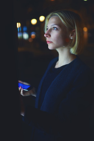 remittances: Portrait of gorgeous young woman realize internet money payment with automated teller machine while holding mobile phone in the hand, female strolling in night city with out-of-focus lights, filter