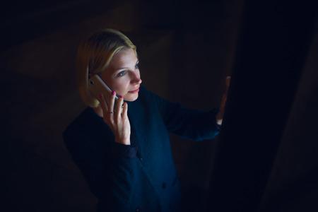 ゴージャスな若い女性のスマート フォンで話すとあなたのテキスト メッセージは、女性の大きなデジタル画面とコピー領域自動預け払い機を使用し