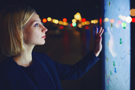 Young female tourist using smart city gadget to get direction in Barcelona central, female in night city standing front big digital screen with city map routes and locations shown on it Stock Photo