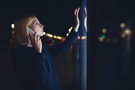 remittances: Young caucasian woman talking on cellphone touching sensitive screen of smart city bus stop in night city with out-of-focus lights, female doing internet money payment with automated teller machine Stock Photo