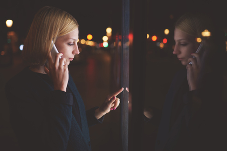 remittances: Young caucasian woman talking on cellphone while touching sensitive screen of smart city bus stop into the night, female using mobile banking or internet money payment through automated teller machine