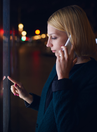 automated teller machine: Tourist girl speaking on cellphone and using automated teller machine with digital screen while standing in night city with out-of-focus lights,woman verifies account balance on banking application Stock Photo