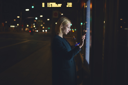television icon: Young blonde female using tourist information self service while standing in beautiful night city with lights on background, pretty woman touching big digital screen of smart bus station of Barcelona Stock Photo