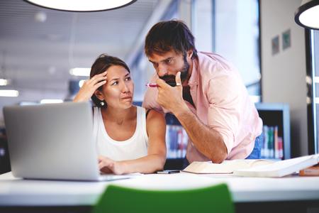 using the computer: Dos trabajadores de oficina hablando en una oficina interior, jóvenes colegas de negocios que discuten el trabajo en un ordenador portátil en el espacio de co-trabajo, la gente de negocios corporativos mirando un ordenador portátil que tiene conversación