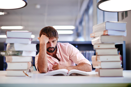 exam preparation: Frustrated male student sitting at the desk with a huge pile of study books in university library, young college student at hard exam preparation in study hall looking tired and weary Stock Photo
