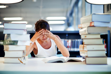 hard work: Frustrated female student sitting at the desk with a huge pile of study books in university library, young asian college student at hard exam preparation in study hall looking tired and weary Stock Photo