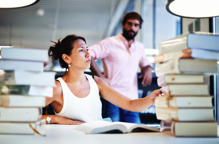 exam preparation: Frustrated college student trying to pull book out of a big stack next to her sitting in university library, young asian female at exam preparation with classmate standing near bookshelf in study hall