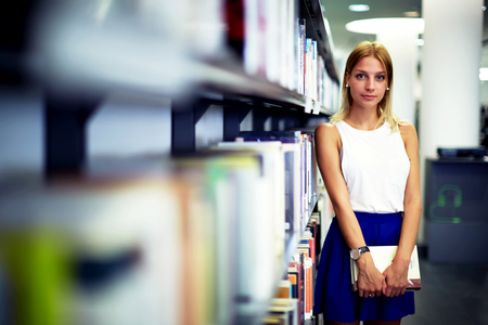 exam preparation: Portrait of a caucasian smiling female student holding book while standing in university library, pretty young woman standing near bookshelves in bookstore shop, exam preparation in university