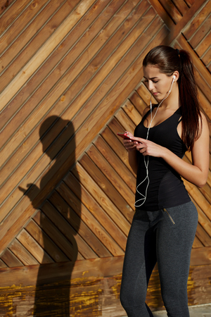 'getting ready': Attractive fit woman in sportswear listening to music with her headphones while training outdoors at beautiful sunny day, young female runner selecting music on cell phone while getting ready for run