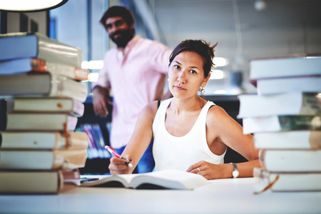 exam preparation: Frustrated college student sitting at the desk with huge pile of study books in university library, young asian female at hard exam preparation with her classmate standing near bookshelf in study hall Stock Photo