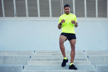 dark skinned: Full length portrait of sporty young man running down a flight of stairs while training outdoors at sunny afternoon,male runner dressed in bright t-shirt working out outdoors while doing legs exercise